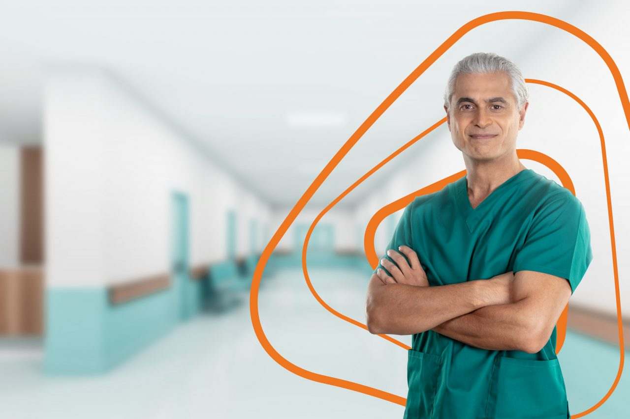 Male doctor standing in front of background